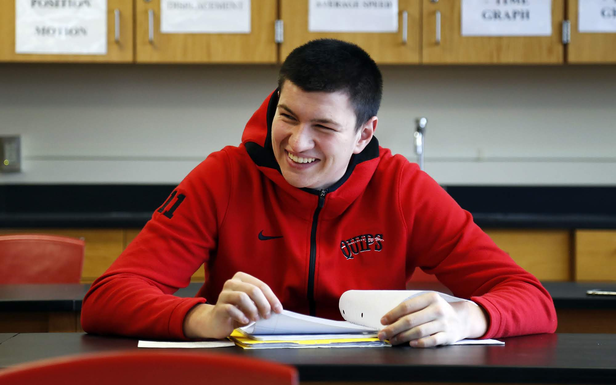 Eli Kosanovich, a senior at Aliquippa Junior/Senior High School laughs and chats with other students before the start of a physics class on Dec. 5, 2018. (Photo by Ryan Loew/PublicSource)